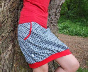 Dámská sukně sportovního střihu. Motiv stylizovaných kytiček tvoří takřka geometrický vzor. Sukni pěkně oživuje červený pas a lemování. Sukně má dvě kapsy na nezbytnosti každé mámy. je to Bájo